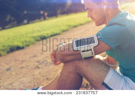 Young Tired Athlete Resting After Workout In The Park, Outdoors