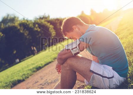 Young Athlete Resting After Workout In The Park, Outdoors