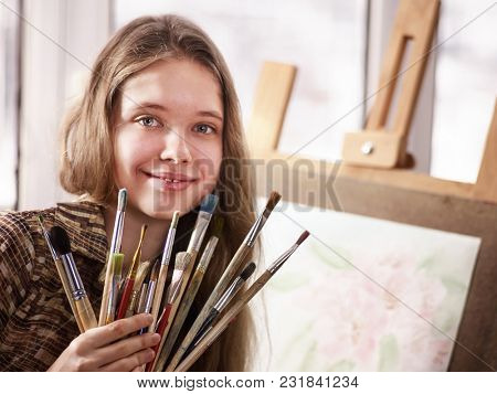 Artist painting on easel and palette in studio. Authentic girl paints with oil brush in morning sunlight . Workshop of a professional artist. Student prepared gift for her teacher.
