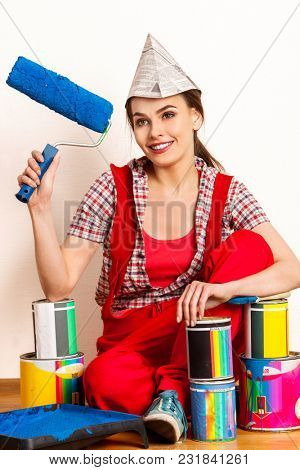 Repair home woman holding paint roller for wallpaper. Aggressive screaming girl in newspaper cap renovation apartment. Loan for housing for students.