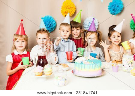 Little Kids Celebrating Birthday. Many Children Near The Table, Friends Are Exciting In The Hours Of