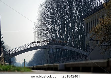 Ancient Bridge Across The Water Canal, River Bank In Old Italy City.