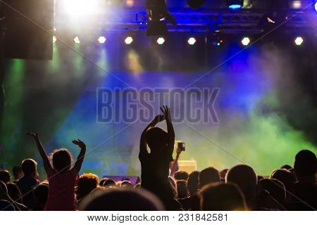 Concert crowd attending a concert, people silhouettes are visible, backlit by stage lights. Raised hands and smart phones are visible here and there.