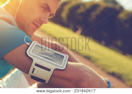 Portrait Of Tired Athlete With Armband Resting In The Park, Outdoors