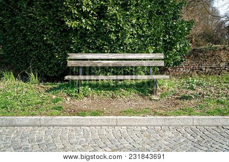 One Wooden Bench On Sunny Day In Italy, Public Parkland.
