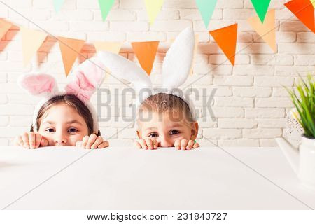 The Cute Kids With Bunny Ears Peeking From Beneath The Table. The Little Boy And Girl Are Waiting Fo