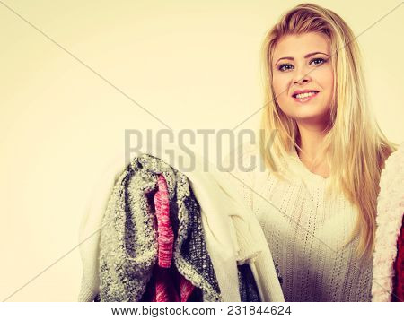 Fashion, Clothes Dilemmas Concept. Young Blonde Woman Teen Girl Holding Big Pile Of Warm Winter Clot
