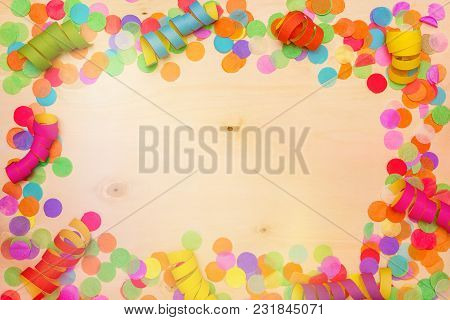 Colorful Confetti And Streamer Lying On Wooden Background With Blank Copyspace As Flatlay