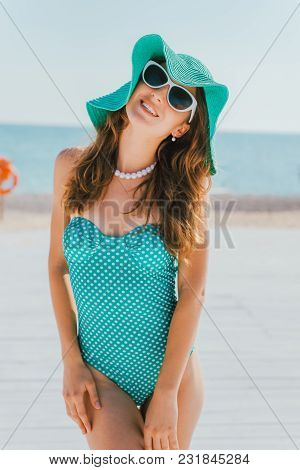 A Woman In A Hat And Swimsuit In Peas Stands Against The Background Of The Sea. Pin-up Style