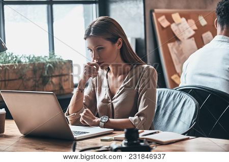 Putting Ideas Into Something Real. Concentrated Young Woman Keeping Hand On Chin And Using Computer
