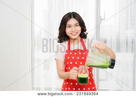 Young Woman Drinking Green Cocktail. Smiling Young Woman With Blender Shaker Jug Pouring Green Veget