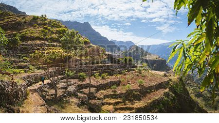 Hiker With Camera Among Agriculture Terraces Nestled Into The Slopes Of Gorgeous Mountains. Trekking