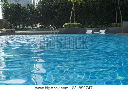 Wimming Pool In Residential Suburb Area House Surrounded By Green Garden And Sunbath Chairs Furnitur