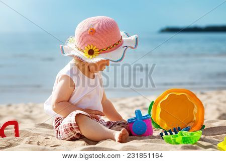 One Year Old Girl Sitting At The Sea With Bucket. Child Outdoors At The Beach In Summer