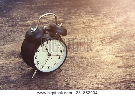 Black Alarm Clock Vintage On Wooden Table And Abstract Nature Background