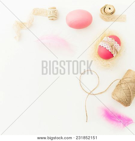Easter Holiday. Frame Of Easter Pink Eggs With Twine, Feathers And Tapes On White Background, Top Vi