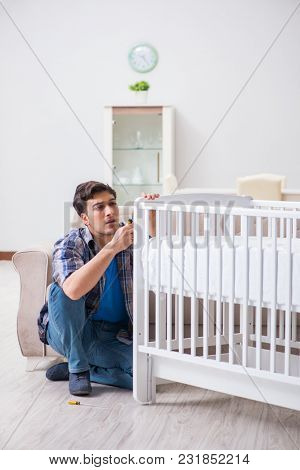 Young man assembling baby bed with instruction manual