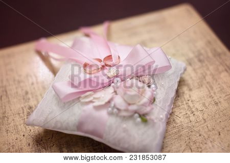 Wedding Rings On A Cushion With Pink Ribbons