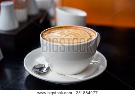 Close Up White Mug With Delicious Cappuccino On Restaurant Table