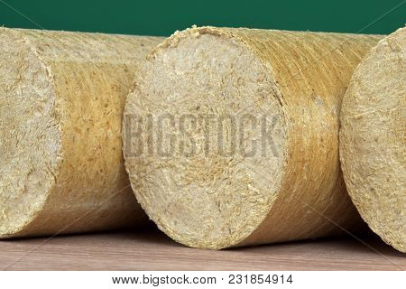 Wood Sawdust Eco-briquettes Straightened, Green Background. Alternative Fuel, Bio Fuel.