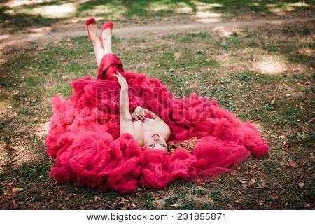 Beautiful Fashion Woman In Red Cloud Dress Laying On The Grass