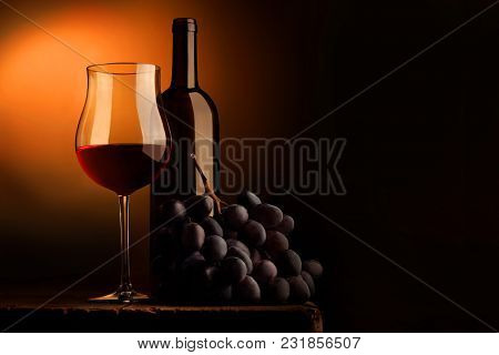 Goblet Of Red Wine With Bottle And Bunch Of Grapes