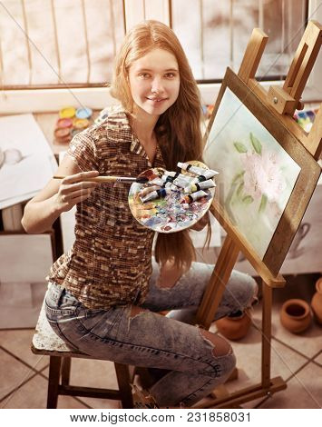 Artist painting on easel in studio. Happy authentic girl paints with brush in morning sunlight dawn light toning. Preparatory courses in drawing for schoolchildren. Young artist gives master class.