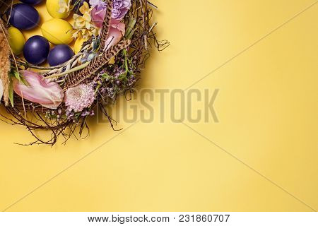 Easter Card. Painted Easter Eggs In Nest On Yellow Table Background. Top View Of Easter Decoration.