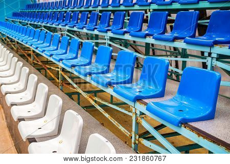 Rows Of Empty Plastic Seats At Sports Center