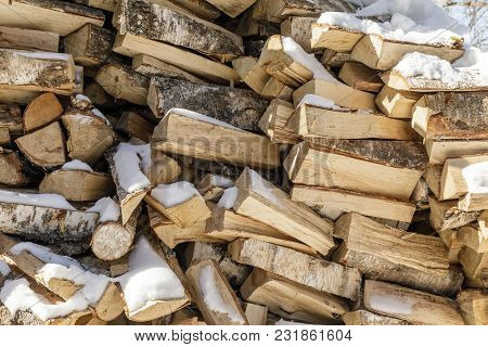 Firewood In Woodpile. Wooden Background.