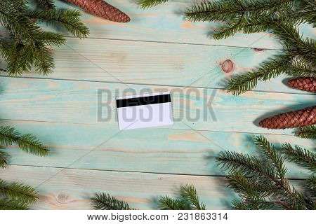 Christmas Background With Spruce Branches And Credit Card On Wooden Board With Copy Space. Online Sh