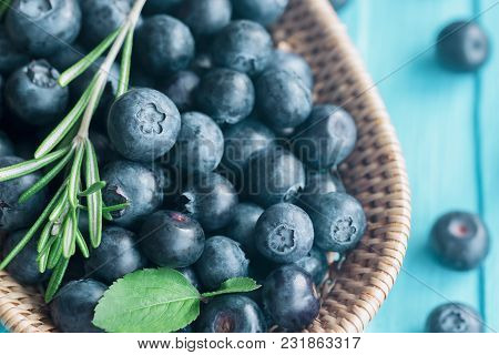 Close Up Fresh Wild Blueberries In Wooden Basket. Ripe Blueberry On Blue Wood Table In Top View With