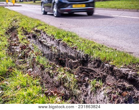 Closeup View Of Car Wheel Tracks Traces In Mud Next To British Road.