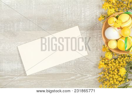 Composition With Painted Eggs. Easter Accessories, Mimosa And Yellow Daffodils On A Light Wooden Sur