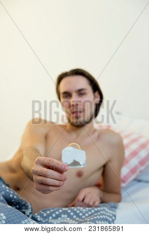 Safe Sex Concept - Man Holding A Condom