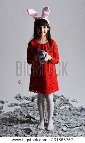 Small Girl Child In Bunny Ears With Many Dollars Money. Business Success, Childhood, Happy Easter. F