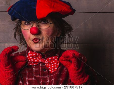 A Portrait Of Clown-woman In Clothes Of Bright Red Color On The Wooden Background.