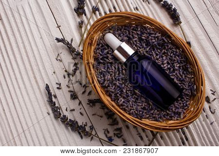 Lavender Essential Oil On A Wooden Background.