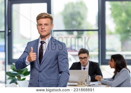 Young Businessman Showing Thumb Up Gesture In Front Of His Colleagues In Modern Office