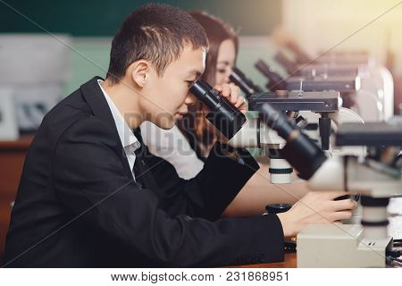 Microscope Asian Student. Man Looks At Microspoon, Analyzes Result. Electron Microscopes Of New Gene