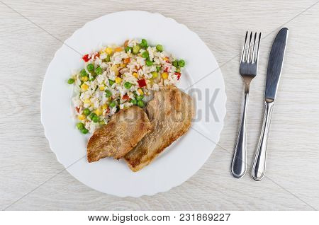 Fried Pork Schnitzel With Vegetable Mix In Plate, Table Knife And Fork On Wooden Table. Top View