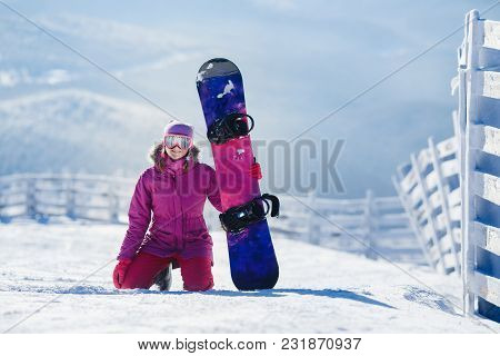 Snowboarding. Young Woman Sits On Snow And Holds Snowboard. Copyspace