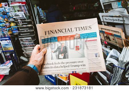 Paris, France - Mar 19, 2017: Man Reading Buying British Financial Times Newspaper At Press Kiosk Fe