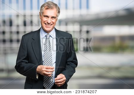 Smiling senior businessman in front of his office