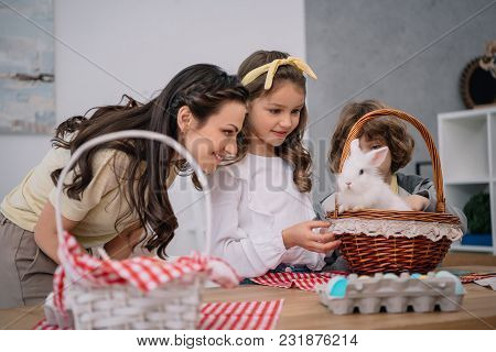 Kids And Mother Playing With Easter Rabbit At Home On Table