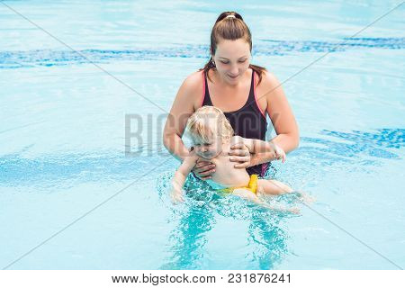 Young Mother Teach Her Little Son, How To Swim In A Swimming Pool.