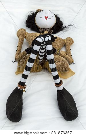 Creepy Steampunk Rag Doll Lying On Back With Knees Raised High Close To Chin. High Angle View. Lifes