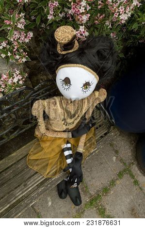 Creepy Steampunk Rag Doll Sitting On Garden Bench. High Angle View. Lifesize Doll On A Grungy White