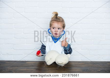 Kid Veterinarian Doctor With Thumbs Up Gesture Diagnose Teddy Bear With Stethoscope On White Wall. H