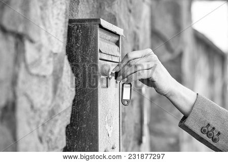 Female Hand Opens Metal Post Box For Correspondance With Key On Mural Background
